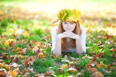 Mujer del adolescente en una guirnalda de las hojas de arce o de mentira Fotografía de archivo libre de regalías