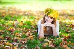 Mujer del adolescente en una guirnalda de las hojas de arce o de mentira Imágenes de archivo libres de regalías