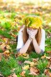 Mujer del adolescente en una guirnalda de las hojas de arce o de mentira Fotos de archivo libres de regalías