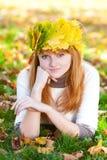 Mujer del adolescente en una guirnalda de las hojas de arce o de mentira Foto de archivo