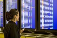 Mujer del aeropuerto con el teléfono celular Imagen de archivo libre de regalías