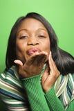 Mujer del African-American que desgasta beso que sopla de la bufanda verde en el viewe Imágenes de archivo libres de regalías