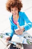 Mujer del Afro con el ordenador portátil y los pulgares para arriba Imagenes de archivo