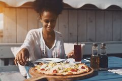 Mujer del Afro que come la pizza en café de la calle Foto de archivo