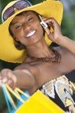 Mujer del afroamericano, bolsos de compras y teléfono celular Imagen de archivo