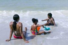 Mujer del afroamericano con los niños que se relajan en la playa Foto de archivo libre de regalías