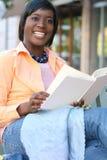 Mujer del afroamericano que lee un libro al aire libre Foto de archivo