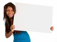 Mujer del afroamericano que lleva a cabo una muestra blanca en blanco Fotografía de archivo