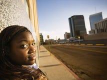Mujer del afroamericano que se inclina contra un edificio Fotografía de archivo