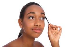 Mujer del afroamericano que usa el cepillo del rimel Fotografía de archivo