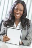 Mujer del afroamericano que usa el ordenador de la tablilla Foto de archivo