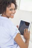 Mujer del afroamericano que usa el ordenador de la tablilla Imágenes de archivo libres de regalías