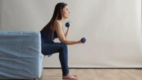 Mujer del ajuste que se sienta en el sofá que hace ejercicio con las pesas de gimnasia, HD lleno