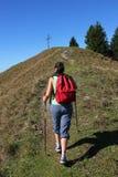 Mujer del alpinismo que camina hacia cruz de la montaña Fotos de archivo
