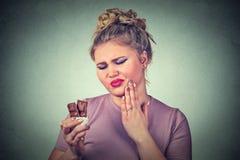Mujer del amante del chocolate con los dientes sensibles del dolor de muelas foto de archivo