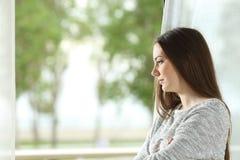 Mujer del anhelo que mira a través de ventana en casa Imagen de archivo