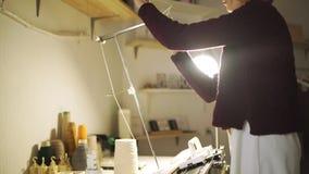 Mujer del arte que tira del hilo en la máquina para hacer punto que se coloca en la tabla en taller almacen de video