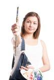 Mujer del artista con la paleta de la pintura que guarda el cepillo Foto de archivo libre de regalías