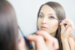 Mujer del artista de maquillaje que hace maquillaje usando el cepillo cosmético para sí mismo Foto de archivo