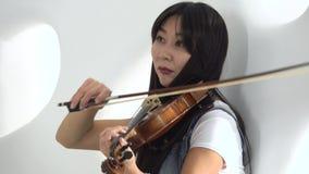 Mujer del aspecto asiático que se sienta en el piso que toca un violín Cierre para arriba metrajes