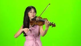 Mujer del aspecto asiático que toca el violín Pantalla verde almacen de video