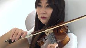 Mujer del aspecto asiático que toca un violín Cierre para arriba almacen de video