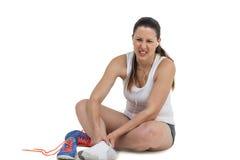 Mujer del atleta con dolor del pie en el fondo blanco Fotografía de archivo libre de regalías