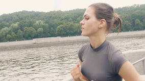 Mujer del atleta que corre en el terraplén en el entrenamiento de la mañana al aire libre metrajes