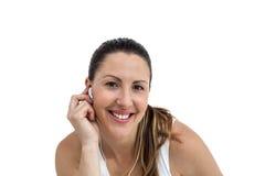 Mujer del atleta que escucha la música en el auricular Fotos de archivo libres de regalías