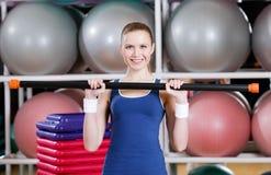 Mujer del atleta que se resuelve con el palillo gimnástico Foto de archivo libre de regalías