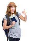 Mujer del Backpacker que sostiene el pasaporte y el dinero con el pulgar para arriba Foto de archivo