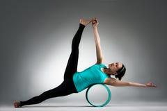 Mujer del bailarín de la yoga que usa el cuerpo de la ayuda de anillo de pilate Fotografía de archivo