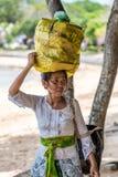 Mujer del Balinese que lleva bendiciendo las bandejas del canang en su cabeza imagen de archivo