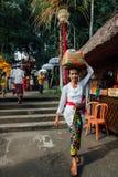 Mujer del Balinese que lleva la caja ceremonial con ofrendas, Ubud, Bali Foto de archivo