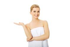 Mujer del balneario envuelta en toalla con la mano vacía Imagen de archivo
