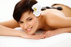 Mujer del balneario. Mujer hermosa que consigue masaje caliente de las piedras Foto de archivo