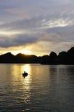 Mujer del barco contra puesta del sol en la bahía de Halong Foto de archivo