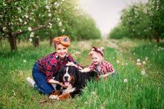 Mujer del bebé con el perro Berna en jardín de la primavera Fotografía de archivo libre de regalías
