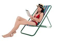 Mujer del bikini que lleva a cabo el dispositivo de la tableta de la pantalla táctil Imagenes de archivo