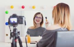 Mujer del Blogger que aplica los cosméticos en la cámara Fotografía de archivo