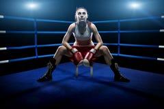 Mujer del boxeo que se sienta solamente en la arena de boxeo, rodeada por las luces azules Fotos de archivo libres de regalías