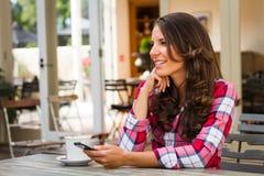 Mujer del café que sostiene el teléfono fotos de archivo