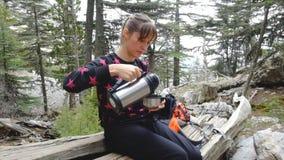 Mujer del caminante que se sienta al árbol caido para tomar un resto y un té caliente de consumición almacen de video