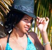 Mujer del Caribe hermosa con el sombrero negro que presenta debajo de la palma Imagen de archivo