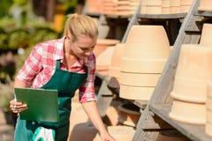 Mujer del centro de jardinería que mira abajo de los potes de arcilla Imagen de archivo