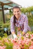 Mujer del centro de jardinería que trabaja en la sonrisa del macizo de flores fotografía de archivo