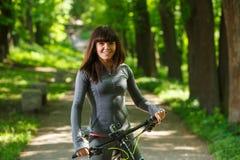 Mujer del ciclista que monta una bicicleta en parque Fotos de archivo
