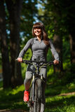 Mujer del ciclista que monta una bicicleta en parque Fotos de archivo libres de regalías