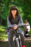 Mujer del ciclista que monta una bicicleta en parque Imagen de archivo