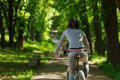 Mujer del ciclista que monta una bicicleta en parque Foto de archivo